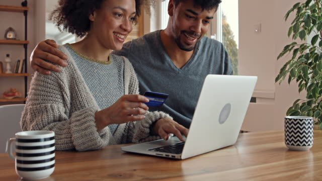 Happy black couple using credit card and laptop for online shopping at home.