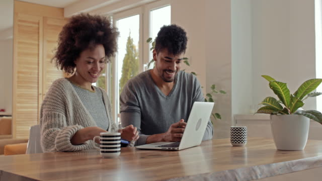 Happy black couple using laptop and shopping on the Internet at home.