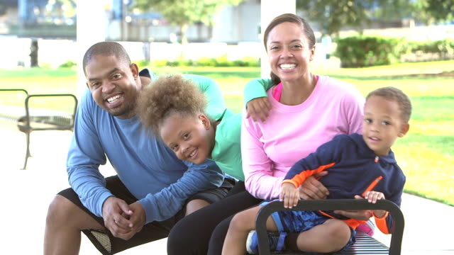 Happy black family with two children sitting on bench