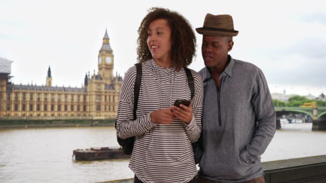 happy black female with her boyfriend using smartphone, standing near big ben - big ben点の映像素材/bロール