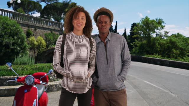 Happy black male and female pose for a portrait with a vespa in Florence