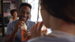 Happy black man on a date at a juice bar with an unrecognizable woman talking while enjoying a juice