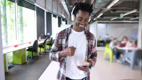 vídeos y material grabado en eventos de stock de hombre negro feliz poniendo en sus auriculares y escuchar música mientras se desplaza hacia abajo en su lista de smartphone - escuchar