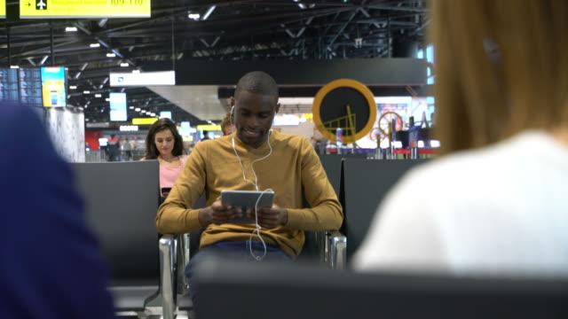 vidéos et rushes de homme noir heureux attendant le vol s'asseyant sur la chaise se relaxant tout en regardant un film sur la tablette utilisant le casque - utiliser une tablette numérique