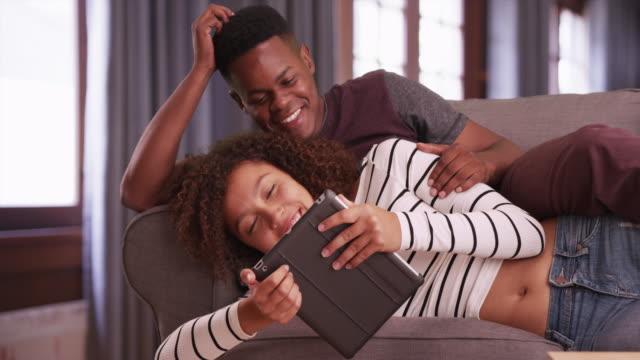 stockvideo's en b-roll-footage met happy black millennial couple watches a video on their tablet - achterover leunen