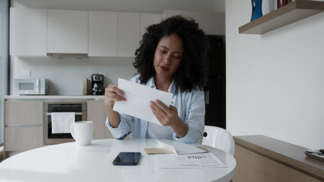 happy black woman at home checking her correspondence - reading mail stock videos & royalty-free footage