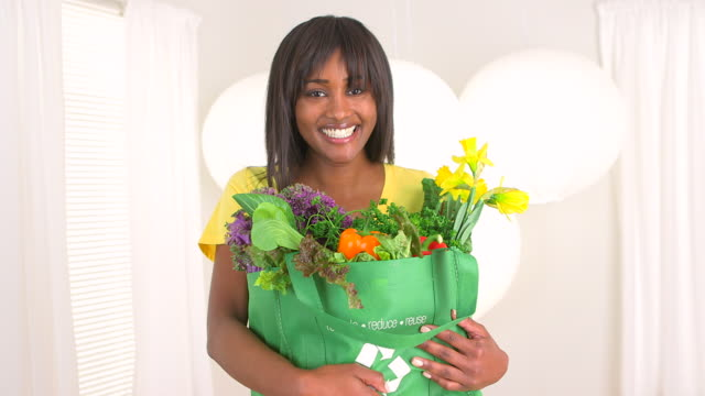 Happy black woman holding groceries