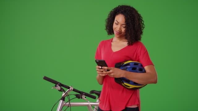 happy black woman using cell phone map app to find bike route on greenscreen - 頭にかぶるもの点の映像素材/bロール