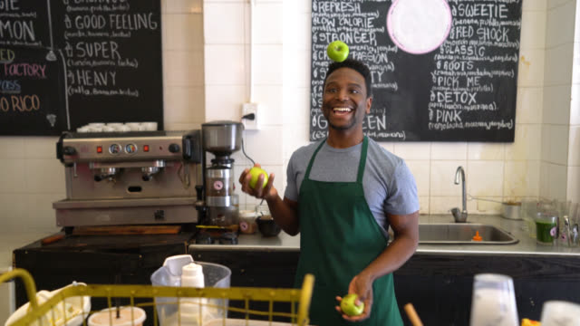 Happy black worker at a juicer juggling with fruits having fun and smiling at the camera