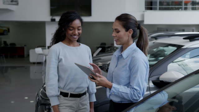 happy black young woman closing a deal with saleswoman at a car dealership handshaking as she hands her the keys - showroom stock videos & royalty-free footage