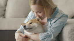 Happy blond woman is playing with pet dog at home next to a sofa.