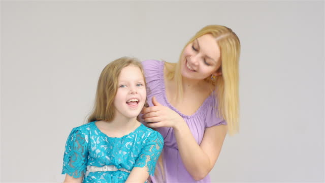 happy blonde mother braids pigtail on daughter's head
