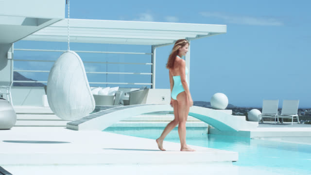 happy blonde woman walks towards luxury pool, plays with her hair and stretches - 美容ケア点の映像素材/bロール