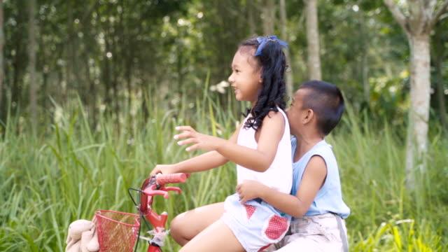 vídeos de stock, filmes e b-roll de menino e menina felizes que jogam e que montam a bicicleta na estrada com riso, conceito da felicidade com slow motion. - estrada de ferro