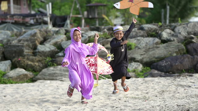 happy boy and girl with kite and laughing boy running on the foreground. - middle east stock videos & royalty-free footage
