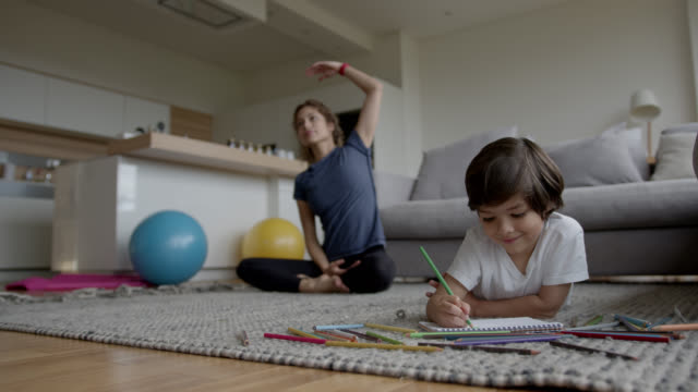 彼の母親がバックグラウンドで運動している間、自宅で着色幸せな男の子 - 南アメリカ点の映像素材/bロール