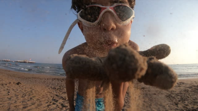 happy boy blowing the sand slow motion - middle east stock videos & royalty-free footage
