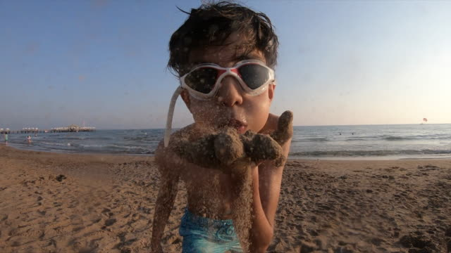 happy boy blowing the sand slow motion - real life stock videos & royalty-free footage