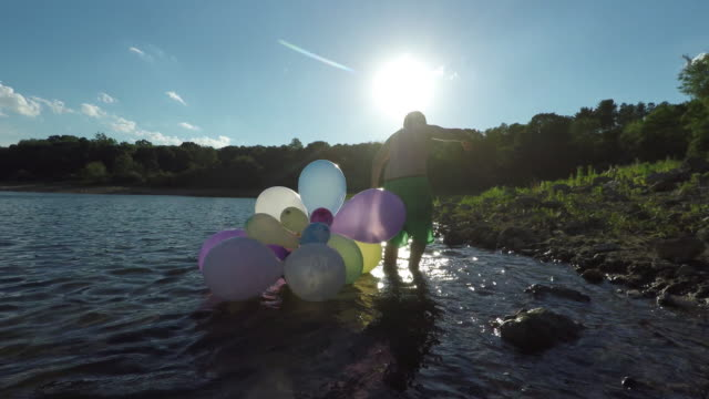 happy boy carrying balloons at the waters edge. - walking in water stock videos & royalty-free footage