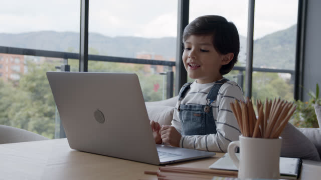 happy boy home schooling during the pandemic using a laptop enjoying his virtual class - preschool stock videos & royalty-free footage