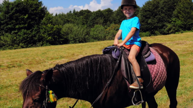 Happy boy in helmet riding brown horse in mountains