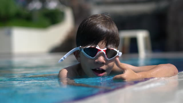 Happy boy in resort swimming pool