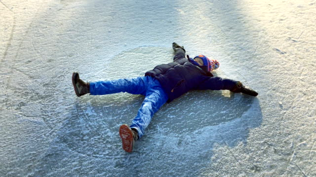 happy boy making snow angel - winter sport stock videos & royalty-free footage