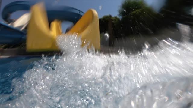 vídeos y material grabado en eventos de stock de chico feliz en los toboganes de agua en el parque acuático - deslizar