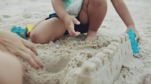 happy boy play sand and happy on the beach with his mother - castle stock videos & royalty-free footage