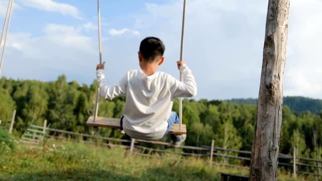 stockvideo's en b-roll-footage met gelukkige jongen spelen op schommel in de achtertuin - schommelen bungelen