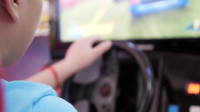 vídeos de stock, filmes e b-roll de menino feliz joga algum jogo de computador, enquanto estiver dirigindo um carro esporte futurista. - controle