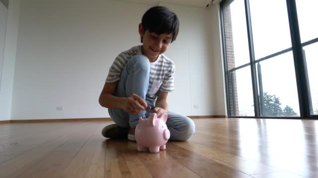 貯金箱のコインを入れ幸せな少年 - 硬貨点の映像素材/bロール