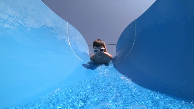 happy boy sliding at water park - water slide stock videos & royalty-free footage