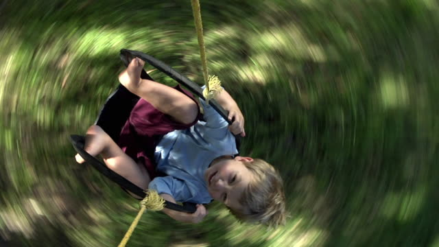 slo mo ms ha happy boy (2-3) spinning around in swing, cape town, south africa - draufsicht stock-videos und b-roll-filmmaterial