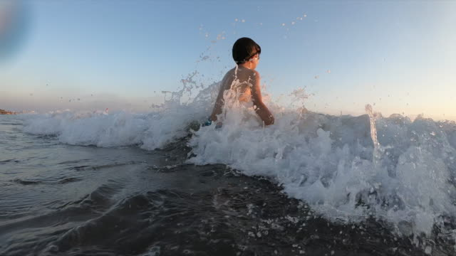 happy boy swimming on the sea making splash - sunbeam stock videos and b-roll footage