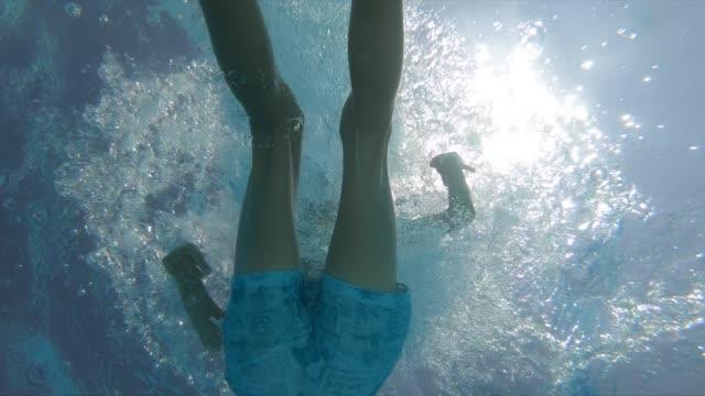 happy boy swimming under the water in resort swimming pool - underwater stock videos & royalty-free footage