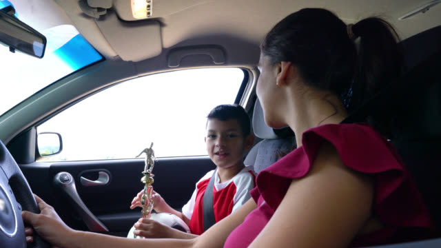 happy boy talking to mom about his exciting football match in the car while holding his trophy and ball - drive ball sports stock videos & royalty-free footage