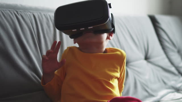 Happy boy using VR glasses at home