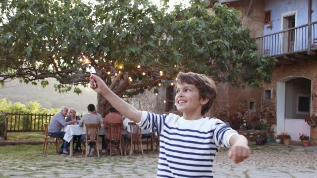 vidéos et rushes de heureux garçon avec sparkler tourne contre la famille - famille multi générations