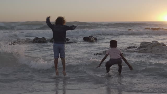 happy boys enjoying in sea waves during sunset - childhood stock videos & royalty-free footage