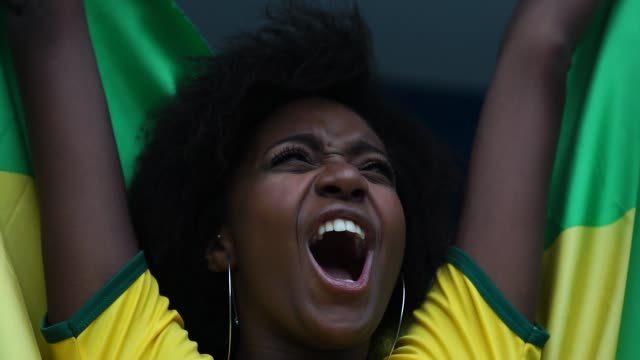 happy brazilian fan celebrating in a soccer game - calcio sport video stock e b–roll