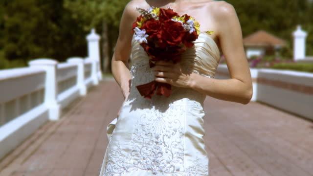 cu tu happy bride in wedding dress holding bouquet, standing on bridge in sunlight, jacksonville, florida, usa - bride stock videos & royalty-free footage