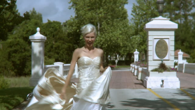 SLO MO MS DS Happy bride in wedding dress running in park, Jacksonville, Florida, USA