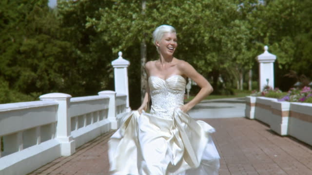 SLO MO MS DS Happy bride in wedding dress running on bridge, Jacksonville, Florida, USA