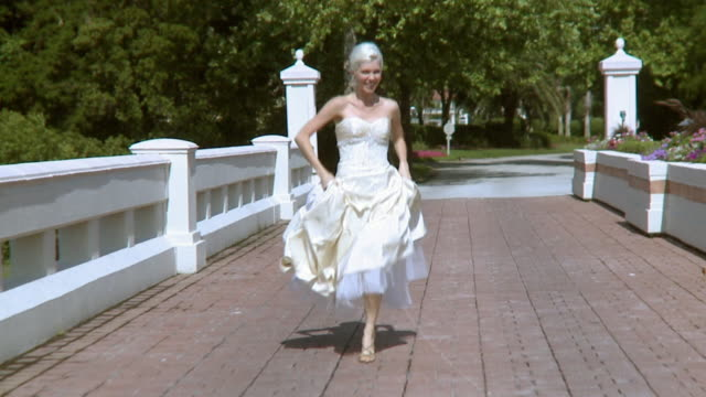 SLO MO WS DS Happy bride in wedding dress running on bridge, Jacksonville, Florida, USA