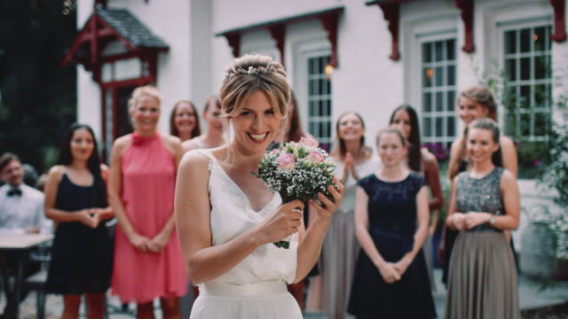 happy bride throwing bouquet to wedding guests - bouquet stock videos & royalty-free footage