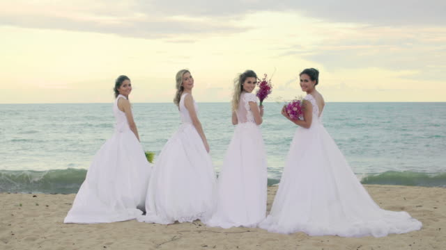 happy brides on the beach. - bouquet video stock e b–roll