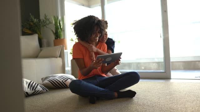 vidéos et rushes de heureux frère et sœur utilisant une tablette numérique ensemble à la maison - frère