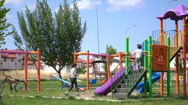 遊び場で滑る幸せな兄弟 - 屋外遊具点の映像素材/bロール