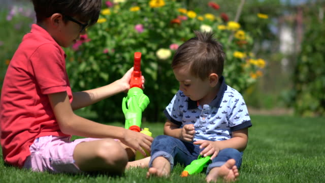 happy brothers playing with water gun on grass - squirt gun stock videos and b-roll footage